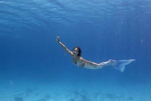 Mermaid Kat swimming underwater in her silicone mermaid tail