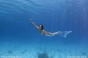 Mermaid swimming underwater in her silicone mermaid tail