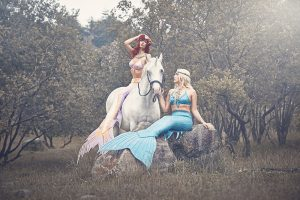 Professional mermaids Kat and Vanessa playing with a unicorn