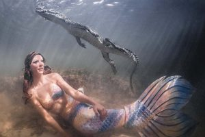 Underwater model and professional mermaid Kat swims with crocodiles